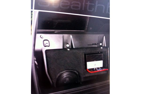 Jl audio stealth box with Jl amplifier behind the seat of a Toyota truck.